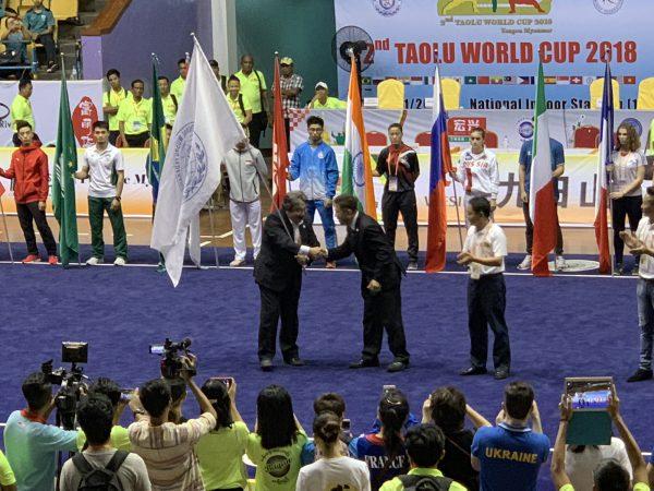 日本代表選手が集体でフィナーレを飾るIWUFの旗を引き継ぐ近藤重和事業委員会委員長